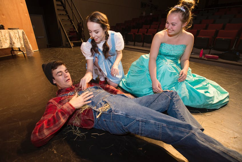 The Scarecrow (Grade 12 student Carson Rafuse) gets some help to re stuff himself from Dorothy (Grade 10 student Sophie MacMillan) and the Good Witch (Grade 12 student Julie Rowe) during a rehearsal for West Kings production of The Wizard of OZ.
