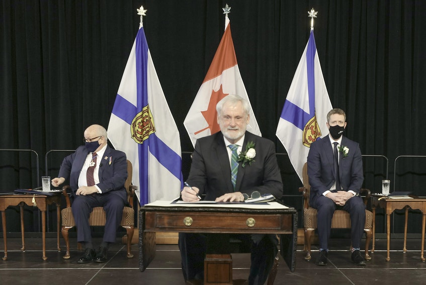 Keith Irving signs the roll Tuesday as minister of environment and climate change, a newly named department. Communications Nova Scotia