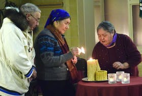 Elizabeth Penashue lights a candle to symbolize healing. Penashue, Ken Mesher (left) and Berta Holieter each lit one on behalf of the survivors of residential schools.
