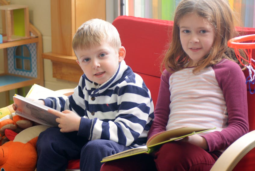 Siblings Cooper, left, and Jorja Bourque read some books during the Family Literacy Day celebration at Montague Rotary Library on Saturday. This year's event encouraged families to read and learn together, with the two Bourque siblings attending the Montague event with their grandfather and town mayor Richard Collins. MITCH MACDONALD/THE GUARDIAN
