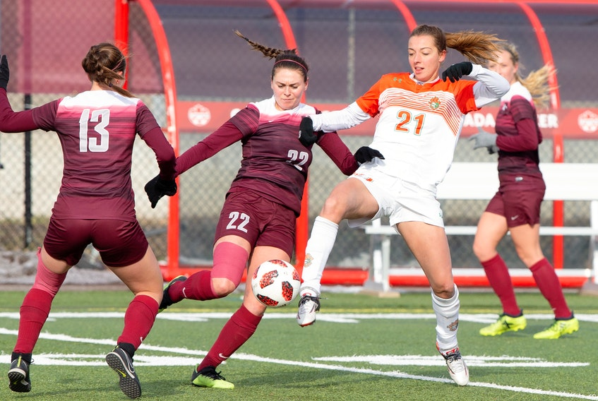 Cape Breton's Rachel Leck battles for the ball against McMaster's Mary Craig (22) and Claudia Continenza (13) during the U Sports women's soccer bronze medal match in Ottawa. Leck scored the lone goal in the Capers' 1-0 victory on Sunday.  U SPORTS PHOTO