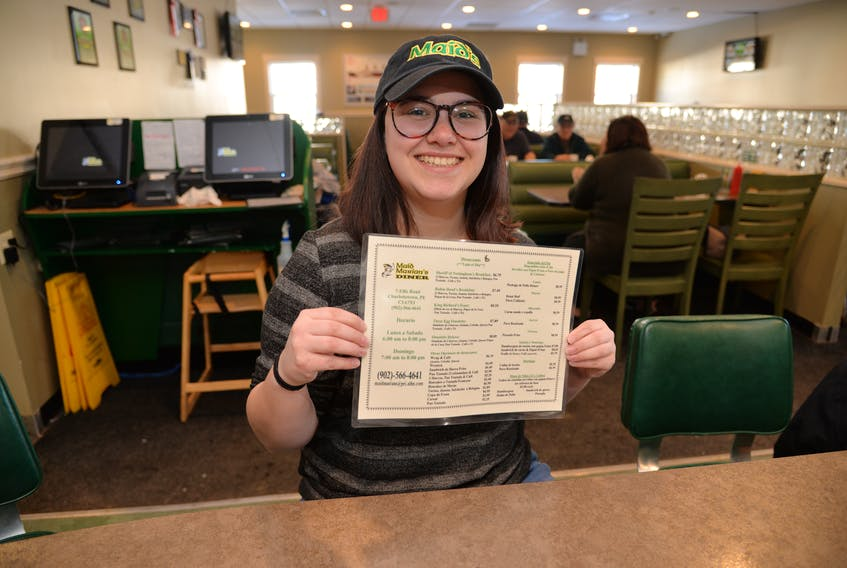 Gabrielle Richard of Maid Marian's Diner holds one of the English-to-Spanish translated menus on Thursday.