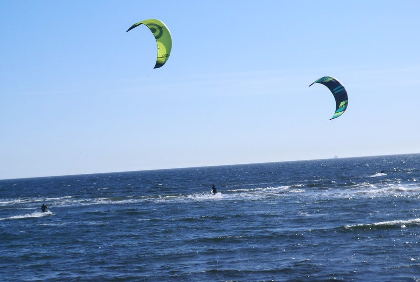 """Bob Doherty and his wife were enjoying the weekend sun around Lawrencetown Beach last Sunday when they spotted these kite surfers from a distance.  He wrote: """" The wind was high and the kites catching the wind almost served as jet like engines  for the surfers. The speed with which they were propelled was  such that  as some of the surfers put on the brakes to turn  at the end of north-south run. They were able to leap several feet in the air before landing back on the water (some of them got dunked doing it but were able to climb back on their boards and start again!).""""  Thank you for the photo, Bob."""
