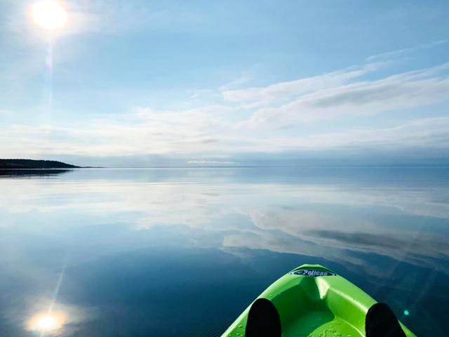 Peace, tranquillity and beauty as far as the eye can see.  Allie Feltmate chose the perfect evening for a paddle off Canso Nova Scotia. The late-day breeze subsided, allowing the perfectly calm waters to reflect streaks of midlevel clouds that dotted the horizon.