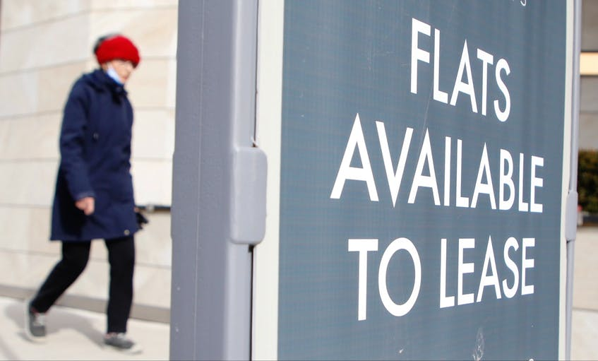 A woman walks by a sign advertising flats for lease in downtown Halifax on Feb. 18, 2021. - Tim Krochak