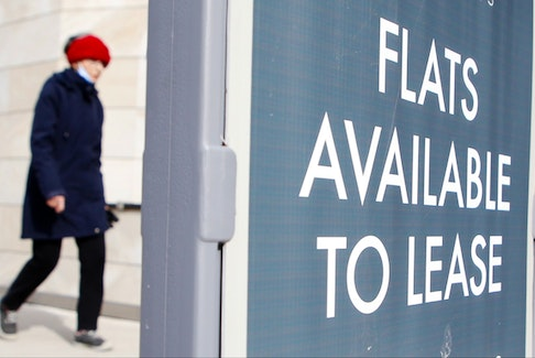 A woman walks by a sign advertising flats for lease in downtown Halifax on Feb. 18, 2021.