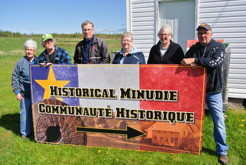(From left) Sharon Gould, Jim Hamilton, David Milner, Sylvia McCoy, Jackie Theal and Dara Legere stand behind one of the new Welcome to Minudie signs that have been erected in the community that overlooks the Cumberland Basin and the River Hebert River. The signs showcase the community's Acadian heritage, while also celebrating the grindstones that Amos 'King' Seaman shipped from an area quarry to the United States.