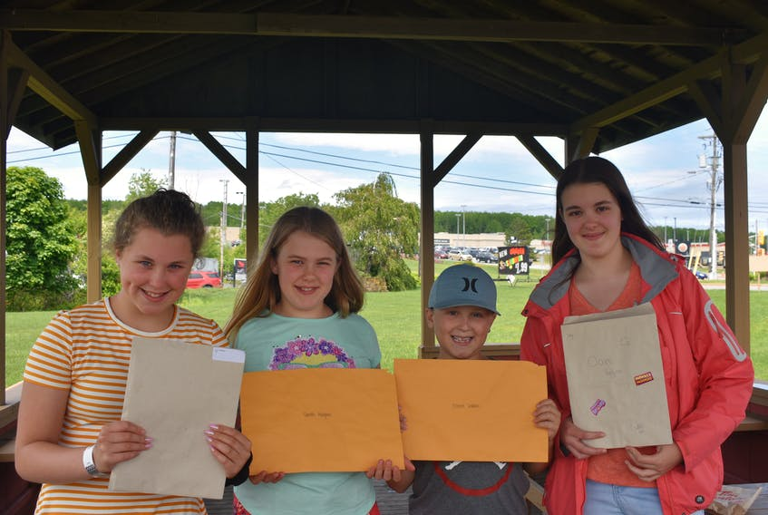 Lily LeBlanc, Sarah Hodgson, Elliott Leblanc and Claire Hodgson hold their report cards proudly after a busy grading day. Together these four joined hundreds of others across Pictou County going from shop to shop getting free sweets and food as a reward for having finished another year of school. Congrats!