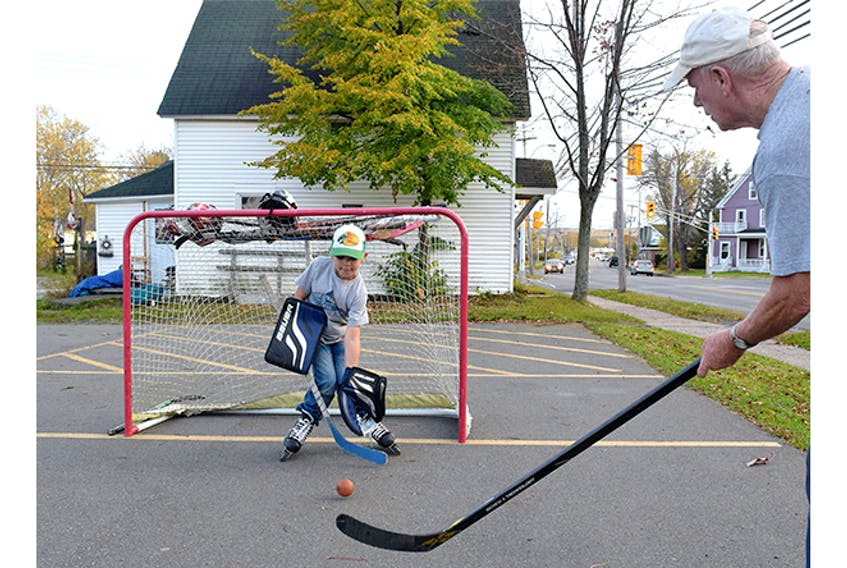Bernie MacDonald take some shots on his grandson Cohen Ross Wednesday night, in an empty parking lot in New Glasgow.