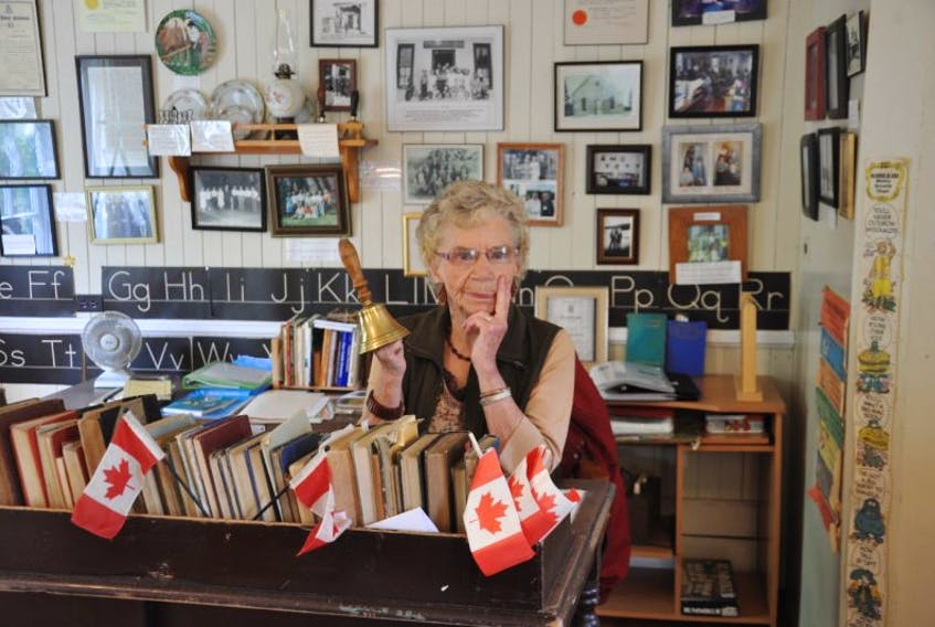 Nova Bannerman, curator of the Barneys River School House Museum, displays a school bell, one of the many historical pieces of interest in the old schoolhouse converted into a community museum, in Barneys River.