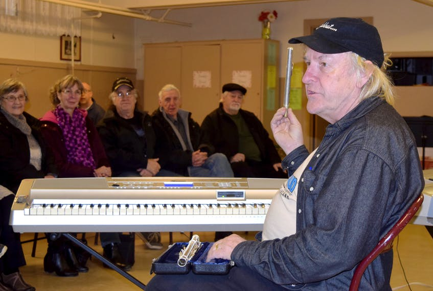 Instructor Paul Barrett demonstrates the flute to prospective members of the New Horizons Band program, at Christ Anglican Church in Stellarton.