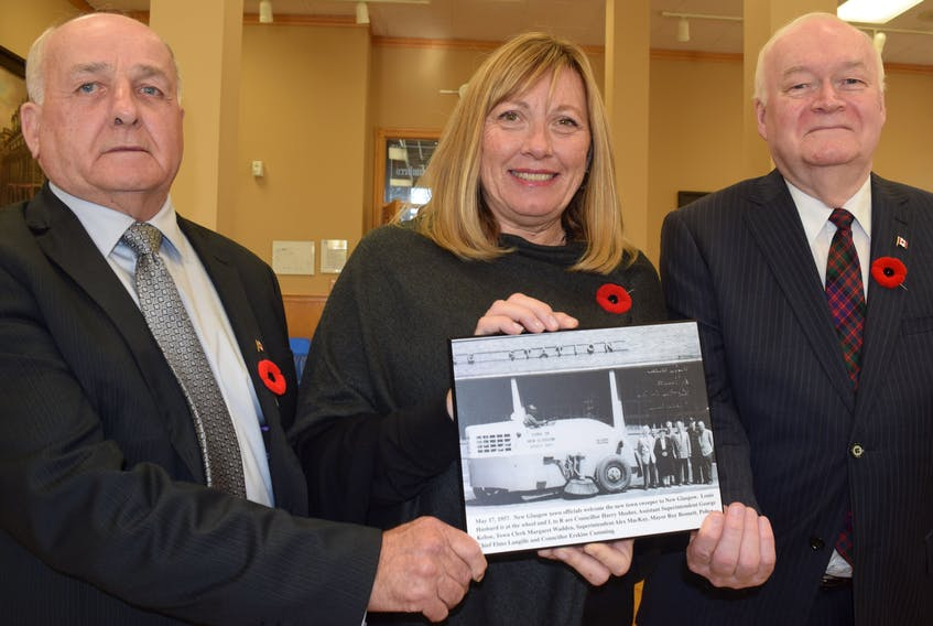 Philip MacKenzie, left, and Clyde Macdonald of the Pictou County Roots Society present New Glasgow Mayor Nancy Dicks with this photo depicting the arrival of a new street sweeper, back in 1957.