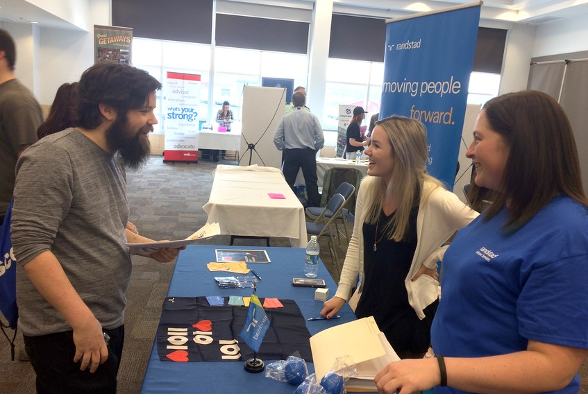 Josh Grant, consults with Leah LeBlanc, upper right, and Erin Wadden with Randstad, on Wednesday afternoon. Grant was one of many people checking out employer tables at the Pictou County 2018 Job Fair.