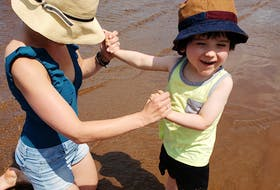 Jennifer Broadbent holds her son Obie's hands as he stands in the water at Pasadena Beach on Sunday. The Corner Brook family used the newly installed Mobi-Mat to get Obie's wheelchair down to the water's edge.