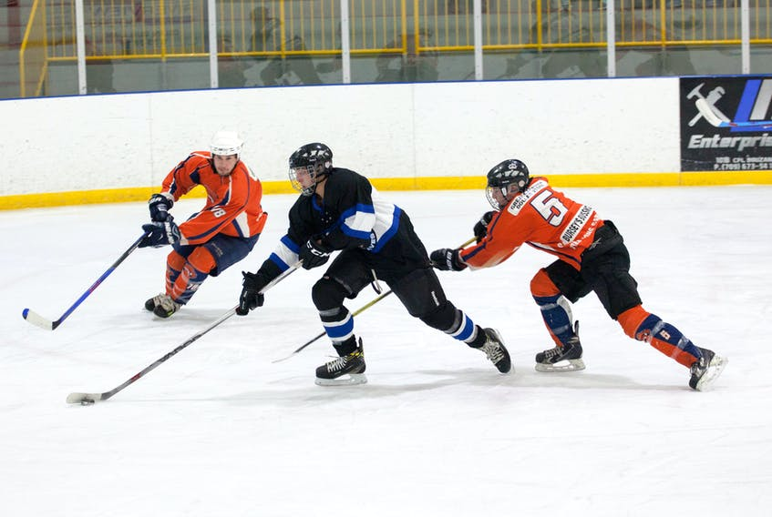 Riley Burt of the Springdale Braves eludes Sabres' defenders Jasper Dicks, right, and Rick Canning in Central Senior Intermediate Hockey League action Sunday in Springdale.