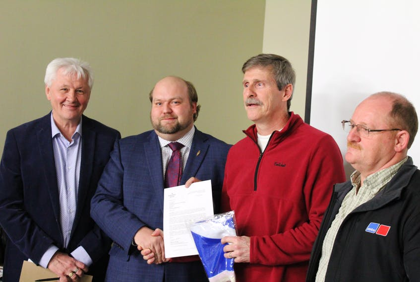 From left to right, Minister of Municipal Affairs and Environment Eddie Joyce, MHA Neil King, LSD chair Craig Pardy, and Morgan Ellis.  King hands Pardy the official letter of approval and a provincial flag.