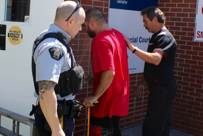 Travis Andrew Firmage is helped by his father into Clarenville provincial court.