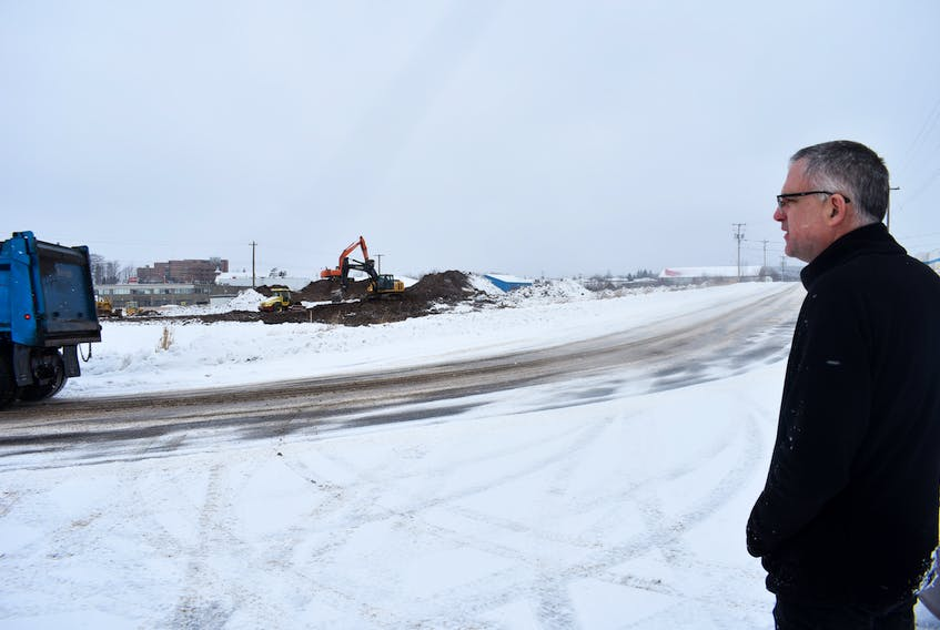 Andy Thompson, director of New Scotland Business Development Inc. and councillor for the Municipality of Pictou County watches work underway on a lot that recently sold in New Glasgow.