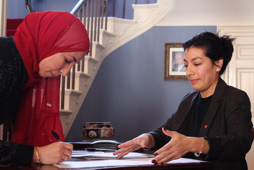 Haidi El Mefary signs herself into Canadian citizenship as Milargos Barrueto, application processing agent for Immigration, Refugees and Citizenship Canada, looks on. - Ernesto Carranza