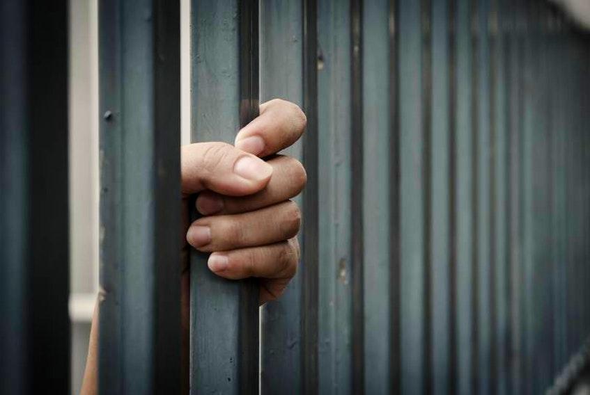 A woman behind bars.