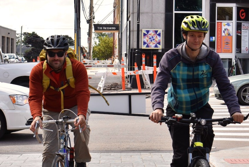 Mitch Underhay, left, and Isaac Williams ride their bikes on Victoria Row. The two members of Bike Friendly Charlottetown want to see e-bikes safely integrated into the existing Island cycling community.