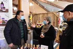 Lily Tran, middle, stops to talk with ElHosseiny ElSherif, left, and James Bunda at the Charlottetown Farmers' Market on Jan. 9.