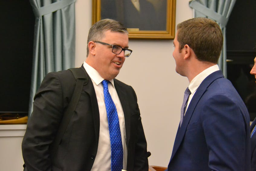 Transportation, Infrastructure and Energy Minister Steven Myers speaks to MLA Corey Deagle in the Coles Building on Tuesday.