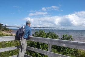 A man at Cape Jourimain, N.B., looks at the Confederation Bridge span towards Prince Edward Island in this stock photo.