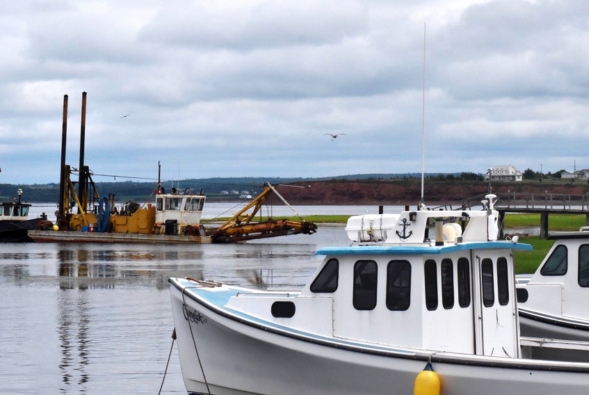 Fishing boats, safely moored at Malpeque harbour, are shown not far from a dredge that is used to try to keep the harbour channel clear so fishers can enter and exit without incident. Plans were recently approved to move ahead with creating a new harbour at Cabot Shores.