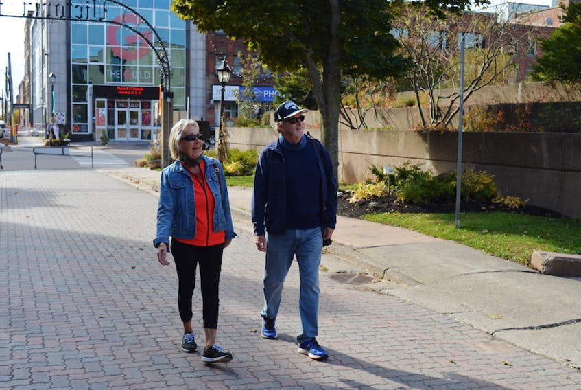 Gabriele Bentley and her husband, Alan, enjoy a walk on Victoria Row on Monday. The Bentleys said they love the idea of making the surrounding area more pedestrian friendly.