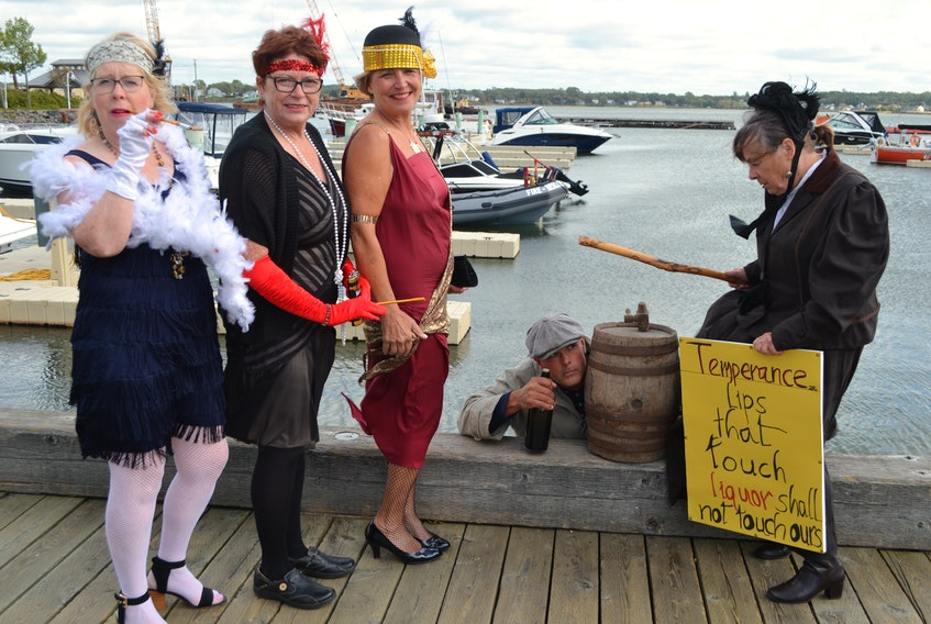 A rum runner (Michael Pendergast), a temperance supporter (Cathy Corrigan) and three flappers create a scene at Peakes Wharf in Charlottetown to promote Glenaladale Heritage Trust's Rum Running Festival. From left are Terry Howatt, Mary Bradley, Cheryl Dalziel and Cathy Corrigan. The festival runs Sept. 27-28 on and near the historical property on Tracadie Bay.