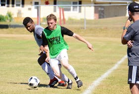 Chukwuka Chibuzo, left, and Kyle Connell battle for the ball along the sidelines in front of the UPEI Panthers men's soccer coaching staff Saturday at Simmons soccer field in Charlottetown.