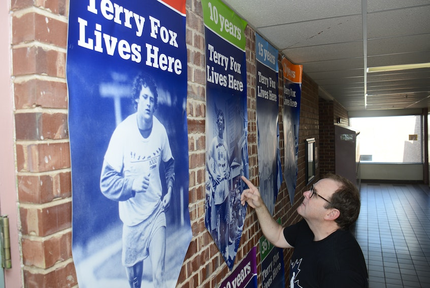 Gordie Cox looks at some of the posters on a wall dedicated to Terry Fox at Colonel Gray High School.