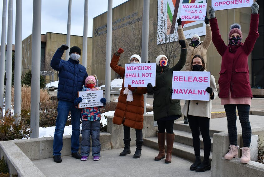 """Protestors hold up signs at a small demonstration in downtown Charlottetown on Saturday. Sporadically, they called out """"release Navalny."""""""