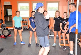 Jacob Arsenault demonstrates an exercise while Brian Arsenault instructs the group of young athletes during a recent training session at Rte. 2 Success in Richmond.