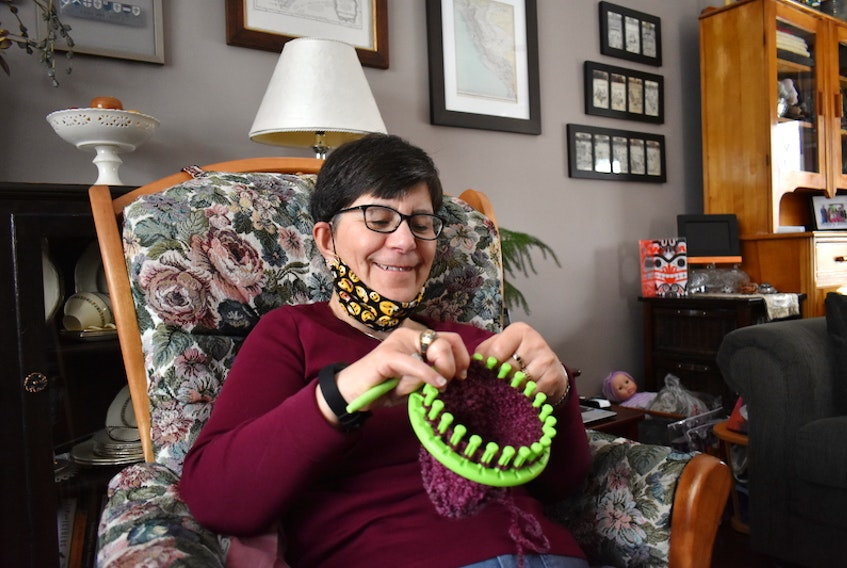 Monique Gauthier smiles while working on a baby cap in her living room. She sits in this chair almost every day to work on the knitted hats she donates.