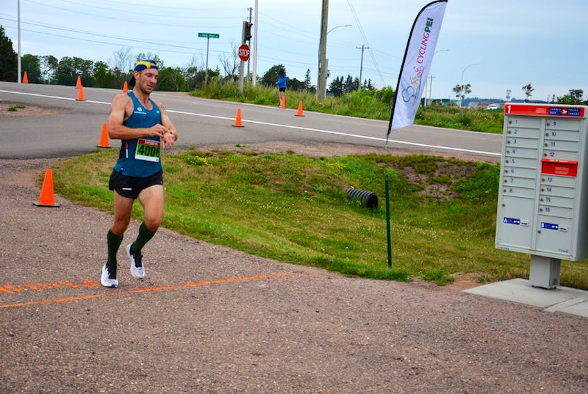 Michael Bergeron of Stanley Bridge check his time as he hits the finish line in the 43rd annual Callbeck's Home Hardware Dunk River Road Race in Bedeque on Sunday morning. Bergeron finished first overall in 40 minutes 59 seconds (40:59).
