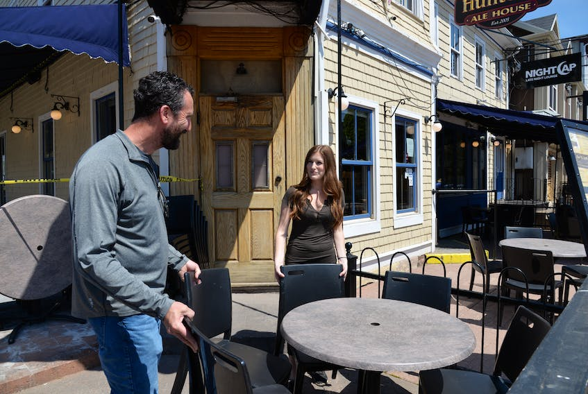 Jeff Sinnott, left, co-owner of the Red Island Hospitality Group Inc., and Hailey McDonald, events co-ordinator, set up the patio on Thursday at Hunter's Ale House in Charlottetown in anticipation of Monday's reopening of dining and patio services.