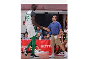 Boston Celtics assistant coach Scott Morrison, right, meets rookie Tacko Fall at the bench.