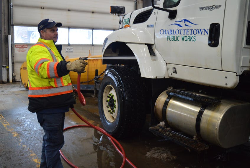 Dean Bradley, who works at Charlottetown's public works garage on MacAleer Drive, hoses his truck down after being out on messy roads on Friday. Conditions are pretty cramped in the few bays public works has, but that's all going to change thanks to the $3 million in the city's capital budget to build a new 12,000-square-foot-building that will house departments currently sharing the space with public works. Dave Stewart/The Guardian