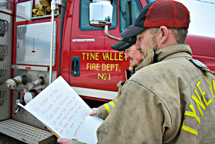 Daniel Grigg, from left, and Andrew Morrison of the Tyne Valley Fire Department read a large 'thank you' card written by the Tyne Valley Tornadoes Peewee A boys hockey team. The young hockey team played many games at the Tyne Valley Community Sports Centre and came early Saturday morning to show their support.
