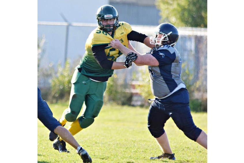 The Summerside Clippers' Landon Gallant fends off a block by a Charlottetown Privateer during a Papa John's P.E.I. Varsity Tackle Football League game.