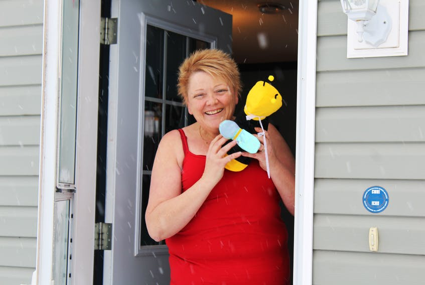 Kim Baglole is shown with her bee bear outside her Southwest Lot 16 home. Baglole started an online activity called P.E.I. Bear Hunt where Islanders put teddy bears in their windows, and parents can go for a drive with their children and try to spot as many as they can.