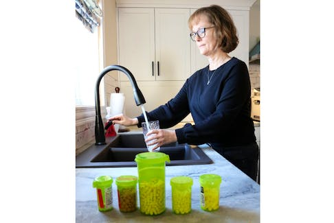 Lisa DesRoches fills a cup of water at the sink. She's got taking her medication for Tarlov Cyst Disease down to a science. Combined with the medication she also works with a pain management doctor. The progressive, chronic disease is something she'll live with for the rest of her life.