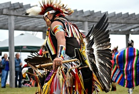 In Mi'kmaq culture, the eagle is the most sacred animal because it flies highest in the sky and carries prayers to the Creator. This dancer proudly displays a wealth of eagle feathers during the Lennox Island powwow.