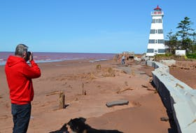 Photographer Lowell Palmer joins other beach-goers in capturing photos to document how hurricane Dorian has altered the look of the West Point beach beside the West Point Lighthouse.
