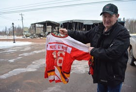 """William Bishop, chief of the Tyne Valley Fire Department, holds up the only hockey jersey salvaged from the Tyne Valley rink fire. He describes the loss, just across the road from the fire hall, as """"disheartening."""" Eric McCarthy/Journal Pioneer"""