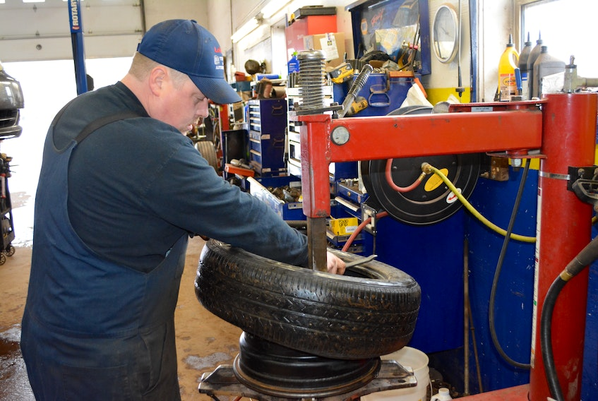 Stephen LeClair breaks a summer tire from the rim as he prepares to replace it with a studded winter tire. LeClair's Tire and Automotive shop had been busy with tire changes all last week, but Thursday night's snowfall shifted the process into high gear.