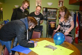 Emily Ramsay adds her message to a poster wishing Vanessa Clements well in the Big Brother Canada house. From left, Mike MacLean and Blair and Cindy Clements.