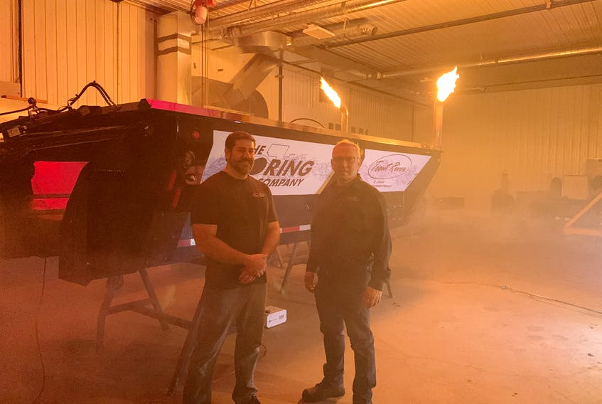 Darrin Mitchell, left, president of Trout River Industries and company founder Harvey Stewart standing next to the modified trailer their company build for the Elon Musk-owned Boring Company.